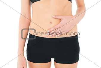 Close-up mid section of a fit woman with stomach pain