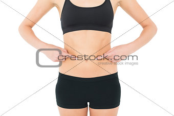 Close-up mid section of a fit woman with hands on stomach