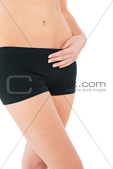 Close-up mid section of a fit young woman in black shorts