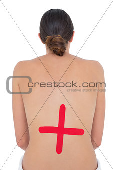 Topless fit woman with red cross sign on back
