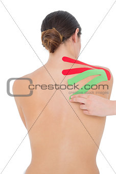 Topless fit woman with red and green strips on shoulder