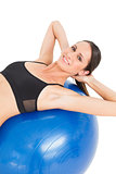 Portrait of a smiling fit woman stretching on fitness ball