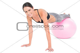 Fit woman doing push ups on fitness ball