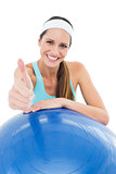 Smiling fit woman with fitness ball gesturing thumbs up