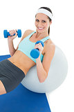 Smiling fit woman exercising with dumbbells on fitness ball