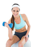 Fit woman exercising with dumbbell on fitness ball