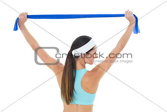 Fit young woman holding up a blue yoga belt