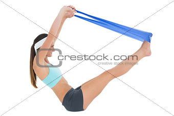 Side view of a fit woman exercising with a blue yoga belt