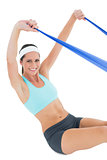 Smiling fit woman exercising with a blue yoga belt