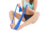 Fit woman exercising with a blue yoga belt