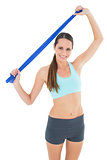 Smiling fit young woman holding blue yoga belt