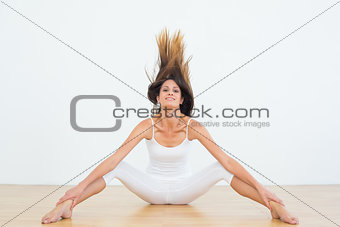 Toned woman tossing hair in fitness studio