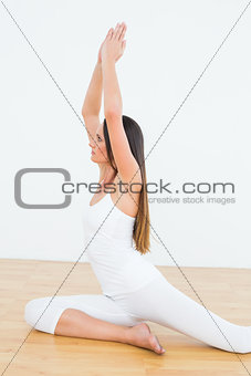 Toned woman with joined hands over head at a fitness studio