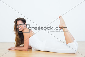 Fit woman lying on floor in the fitness studio