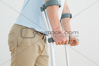 Close-up mid section of a man with crutches