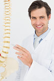Portrait of a smiling doctor with skeleton model