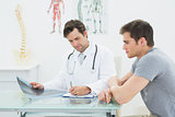 Male doctor writing reports besides patient