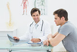 Smiling male doctor writing reports besides patient