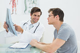 Smiling male doctor explaining spine x-ray to patient