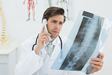 Doctor with spine x-ray picture using the telephone