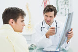Doctor explaining spine x-ray to patient in office