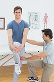 Male therapist assisting a man with stretching exercises