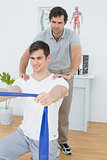 Male therapist assisting young man with exercises