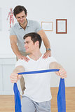 Male therapist assisting man with exercises in office