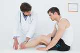 Side view of a young man getting his ankle examined