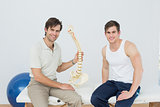 Male physiotherapist explaining the spine to patient