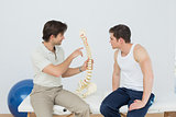 Physiotherapist showing patient something on skeleton model
