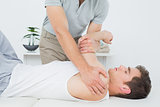 Male physiotherapist examining a mans hand