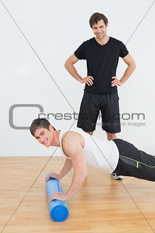 Portrait of physical therapist with young man doing push ups