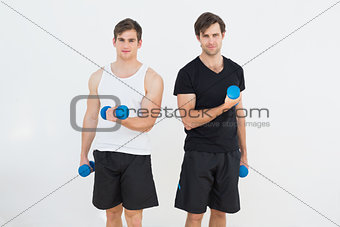 Portrait of two smiling young men with dumbbells