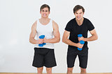 Two young men flexing muscles with dumbbells