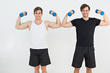Portrait of two young men flexing muscles with dumbbells