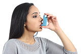 Asthmatic arab woman breathing from a inhaler