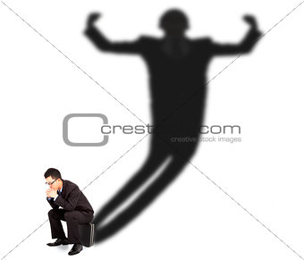 Business man sitting and casting shadow of a strong man