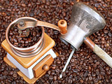 coffee grinder and copper pot on roasted beans