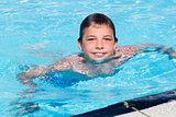 Activities on the pool. Cute boy swimming and playing in water i