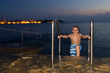 Night shot of boy getting out of the sea against the resort town