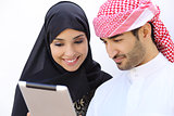 Happy saudi arab couple looking a tablet together
