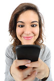 Wide angle view of a pretty teenager girl happy with a smart phone