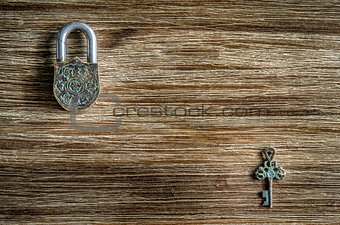 Closed vintage padlock and key on a wooden texture