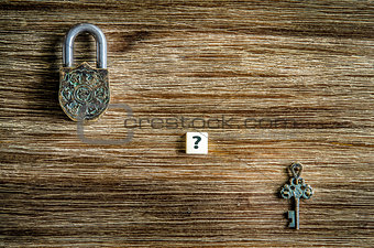 Old vintage padlock and key on wooden texture