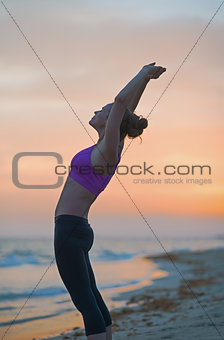 Fitness young woman making exercise on beach in the evening