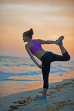 Fitness young woman stretching on beach in the evening
