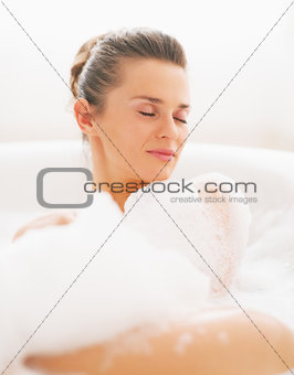 Portrait of young woman laying in bathtub