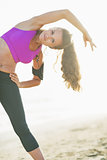 Fitness young woman making exercise on beach