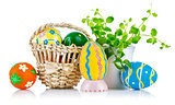 easter eggs in basket with spring leaves